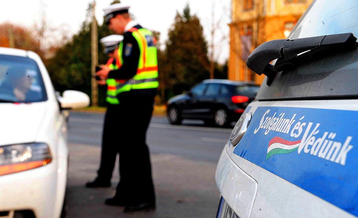 Fényvisszaverő mellényeket osztanak a rendőrök egy akcióban